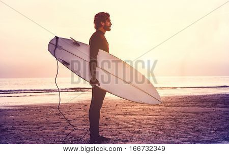 Man surfer carrying his surfboard at sunrise - Hipster male in wetsuit waiting for the high waves on beach - Extreme sport concept - Focus on silhouette - Matte filter with soft blue vignette