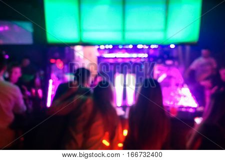 Blurred people sitting at bar counter inside disco club - Original colors lights in background - Defocused image - Concept of nightlife with music and entertainment - Warm vivid filter