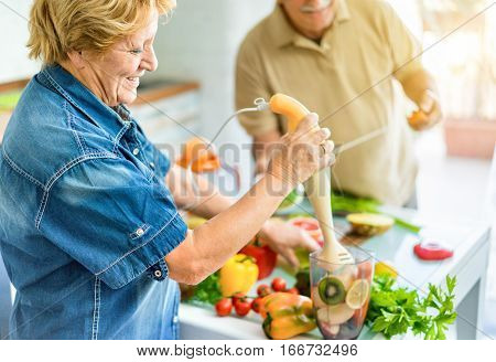 Senior couple cooking healthy vegetarian meal with fruits and vegetables together - Old happy people taking care about diet and health - Vegan and bio concept - Focus on woman eye - Warm vivid filter
