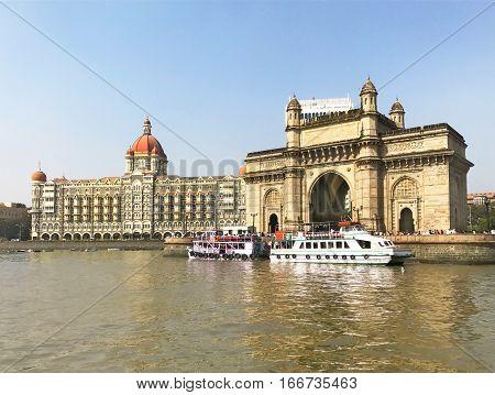 MUMBAI INDIA - JANUARY 11 2017: Taj Mahal Palace Hotel and Gateway of India. Both structures in Mumbai Harbor overlook the Arabian Sea.