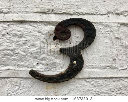 Number three painted black metal house address sign screwed into painted white brick wall textured background