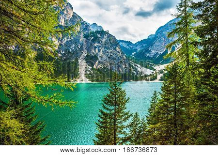 Beautiful lake Lago di Braies. South Tyrol, Italy. The concept of walking and eco-tourism. Green expanse of water reflects the surrounding mountains and forest