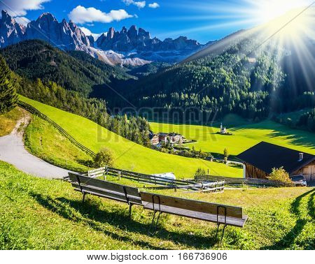 The bright morning sun illuminates the green valley, rural scenic farm and the church.  The concept of eco-tourism in Alpine meadows. Rural dirt road