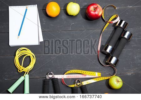 Fruit and dumbbells. Fitness, healthy lifestyle on a black wooden background