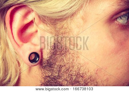 Stretched lobe piercing grunge concept. Pierced man ear with black plug tunnel