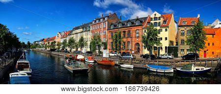 Stockholm, Sweden - January 13, 2010: picturesque embankment along water channel waterway street with historic buildings of old town or city on sunny summer day on blue sky background
