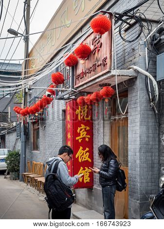 Beijing, China - Oct 30, 2016: Yue Bin Restaurant (悦宾饭馆) is along Cuihua Hutong (old alley or street). Well known to locals for its cheap and delicious food, it is now also popular with visitors from afar. Two people wait outside the entrance.