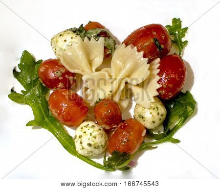 Heart Shape Food made with love background for healthy nutritional eating traditional tomato bocconcini cheese with pesto and pasta and arugula for happy valentines day healthy heart or social media image background card