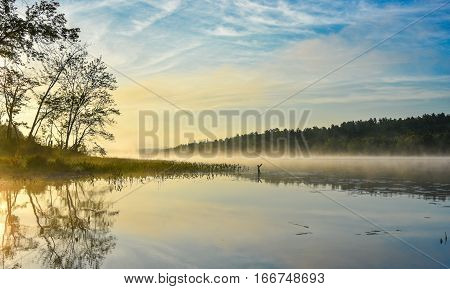 Brilliant and bright mid-summer sunrise on a lake.   Warm water and cooler air at daybreak creates misty fog patches.  Still water along a calm, quiet Ontario lakeside. poster