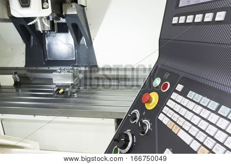 The face milling tool with the raw material work piece on the CNC milling machine in the silver tone effect and the controller panel