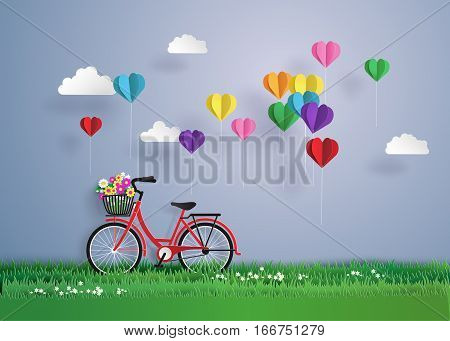 Bicycle in the garden with colorful hot air balloon heart shap.origami and paper art style.