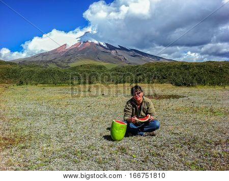 Traveler Caucasian woman eating a watermelon on the foothills of Cotopaxi volcano Ecuador South America