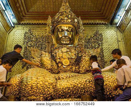 MANDALAY, MYANMAR - NOVEMBER 30, 2016 : people recovering the golden buddha of Maha Myat Muni Pagoda temple Mandalay city Myanmar