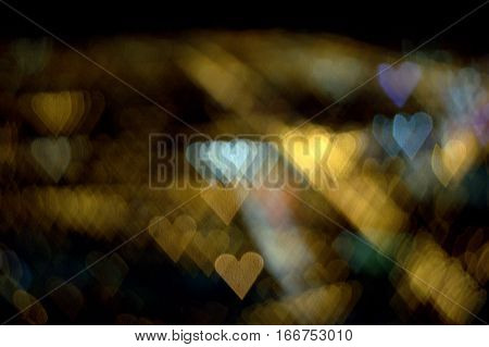 a bunch of hearts of gold and white on a bokeh effect abstract background