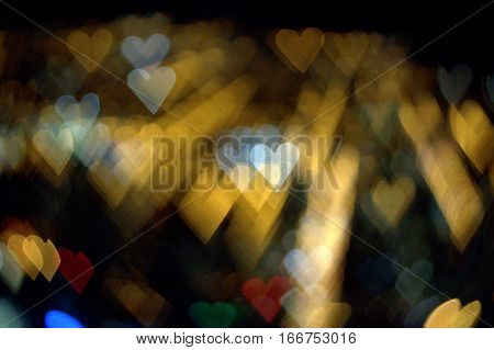 rows of hearts in gold and white on an abstract bokeh effect background