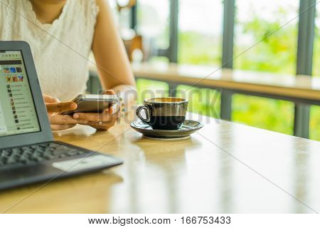 Women's hands holding smartphone with coffee on notebook place on the table with blank copy space screen for your advertising text messageWoman with cellphone in hands while sitting in modern cafe