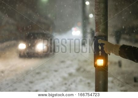A pedestrian pressing the button to start the green light to cross the road during strong snowfall.