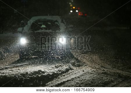 Cars driving on the road in the aggravated traffic due to strong snowfall. poster