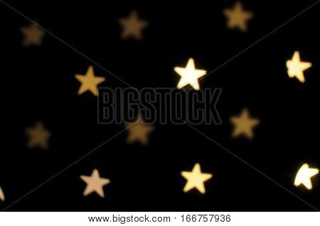 rows of stars five pointed golden bokeh effect dark black background
