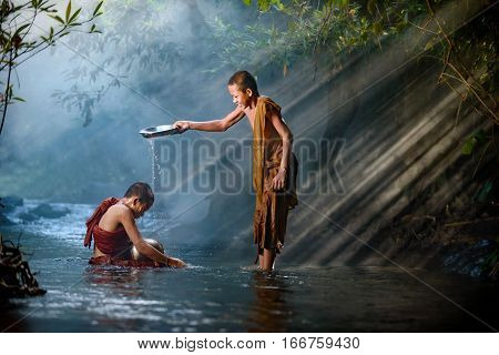 novice monk Thailand are bathing in creek happily with stunning sunlight background