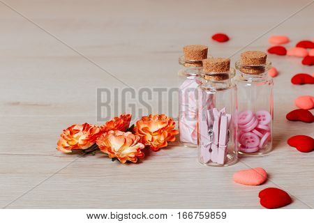 Valentine or holiday composition: close up of bright small hearts spring flowers and glass with contains clothespins and buttons on wooden background. Copy space for text.
