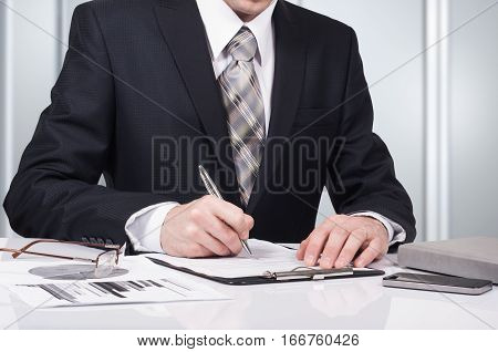 Young businessman signing a contract in office. The concept of a successful business.