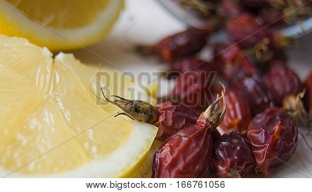 Dried rosehips scattered on the table fresh lemon