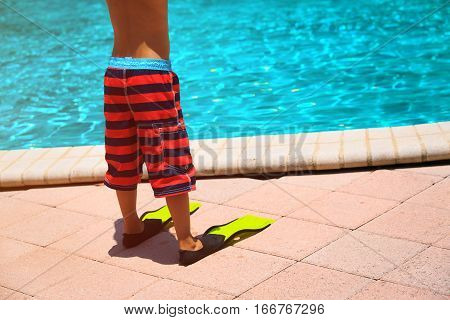 little boy with fins go swim at pool or beach, active kids