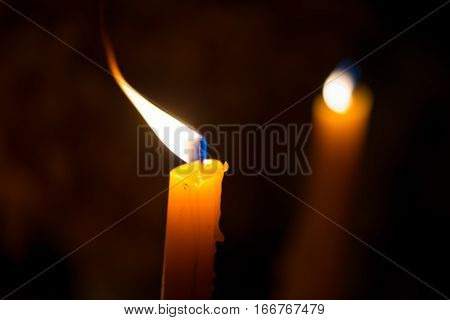 Close-up macro detail of two orange candles with a beautiful flickering flame. Peace and rememberance concept.