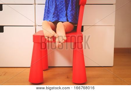 kids curiosity and safety concept- little girl climbing on baby chair to reach new toy