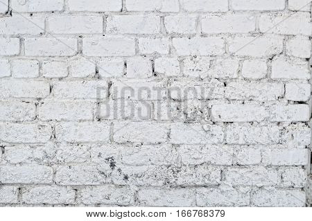 Old grunge brick white wall background. Retro Whitewashed Old Brick Wall Surface. Grungy Shabby Uneven Painted Plaster. Whiten Facade.Design Element.