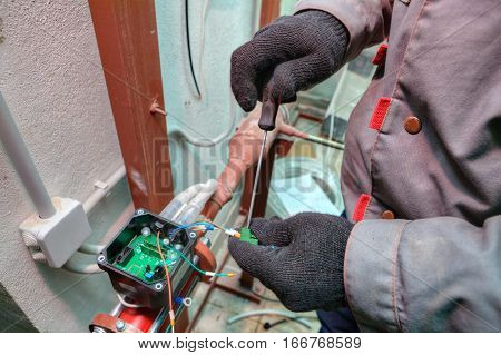 Mechanic engineer installs equipment for central heating systems in apartment building.