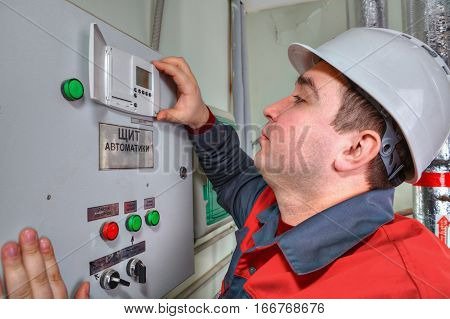 St. Petersburg Russia - March 5 2013: Engineer electrician inspects the electrical panel readings switchboard.