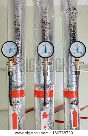 Three pressure gauge in a boiler room next to the hot water pipe in the insulation coating.