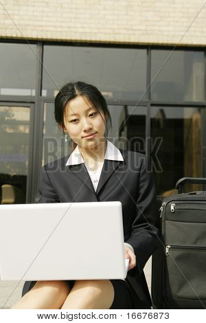 business women workin? with laptop and travel luggage