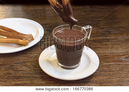 A photo of churros, traditional Spanish, and especially Madrid, dessert, particularly for Sunday breakfast, dipped into hot chocolate. With a place for text