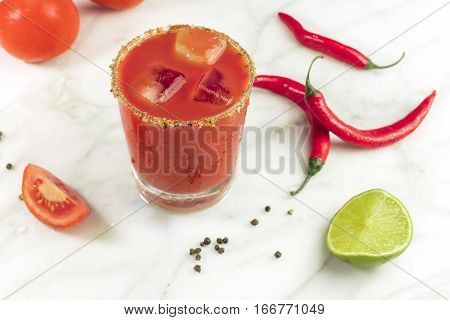 Bloody Mary cocktail on a white marble texture, with red hot chili peppers, slices of lime, and a piece of tomato
