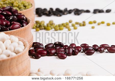 Assortment of haricot in a wooden bowls macro with copy space on white wood background. Healthy protein food.