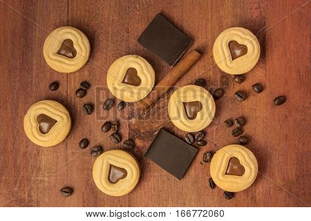 An overhead shot of pieces of chocolate, cocoa cookies with heart-shaped fillings, coffee beans and a cinnamon stick, scattered on a dark wooden background