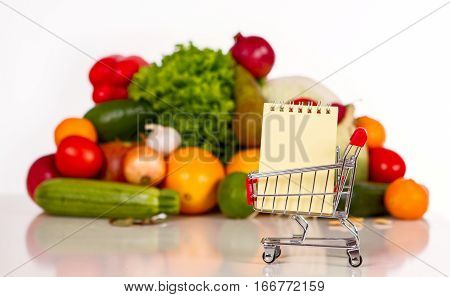 shopping list in a food shop: fruits and vegetables in the background. in the foreground grocery trolley with a notebook and pen