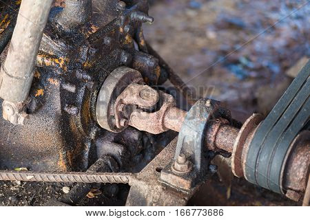Part of the old rusty gearbox and drive shaft with grunge oil dirty Vintage engine car system.