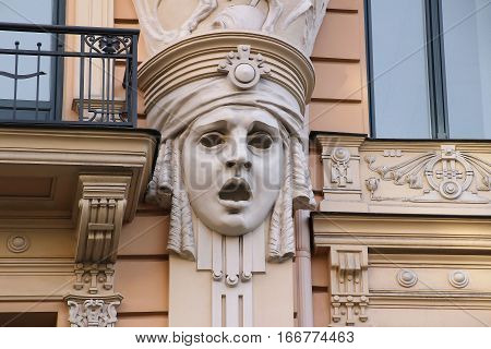 Facade of old building with sculptures of woman heads in Art Nouveau style, Jugendstil. Riga, Latvia.