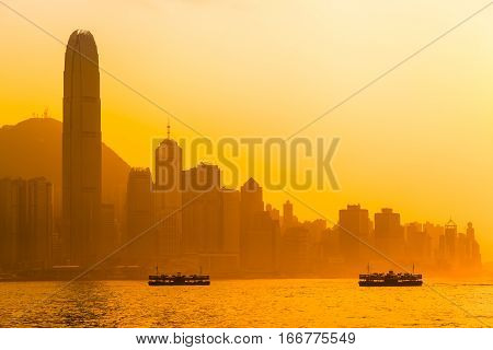 Beautiful Hong Kong cityscape view at orange sunset light with two ships, tall buildings and Peak mountain (copy space)