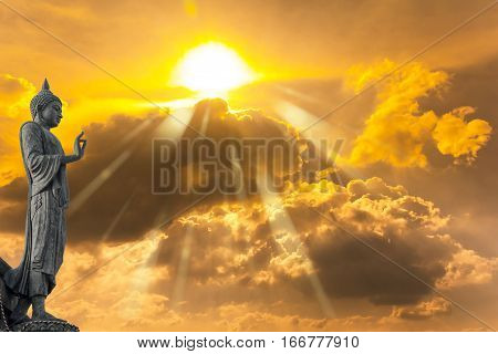 Buddha Statue Against On Golden Sky With Sunlight In Background.