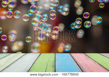 Empty painted wooden table or plank with bokeh of rainbow soap bubbles from the bubble blower on background for product display.