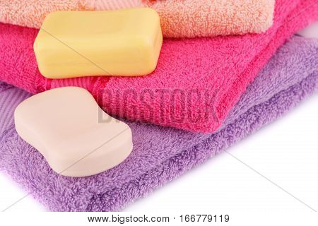 Colorful towels stack and soaps closeup picture.