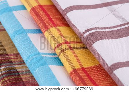 Stack of colorful kitchen towels closeup picture.