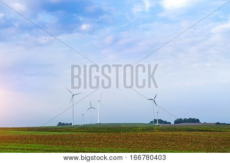 Windmills rotate blades over arable fields and farmland. Electric wind generators produce environmentally clean electricity using wind power. Foggy dawn on early summer morning in village. Rural landscape without people. Taurage district Lithuania Europea