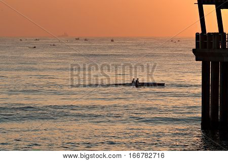 Paddlers on the ocean near a pier at sunrise.