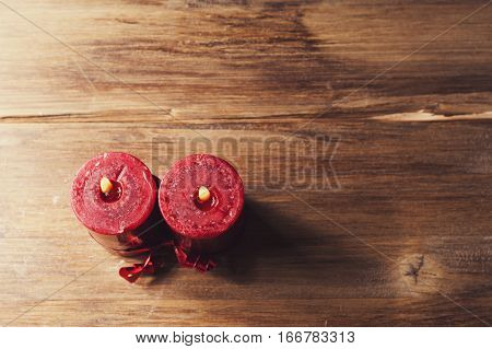 Two red candles tied with red ribbon the symbol of Valentine's day mimics the relationship of men and women on wooden background from old boards